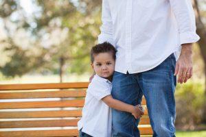 A boy holding onto a father figure.